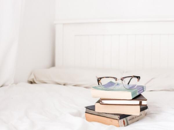 stack of books and glasses on bad
