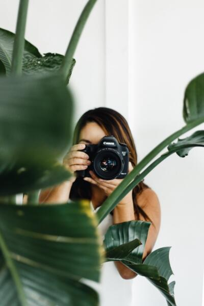Woman holding camera behind plant