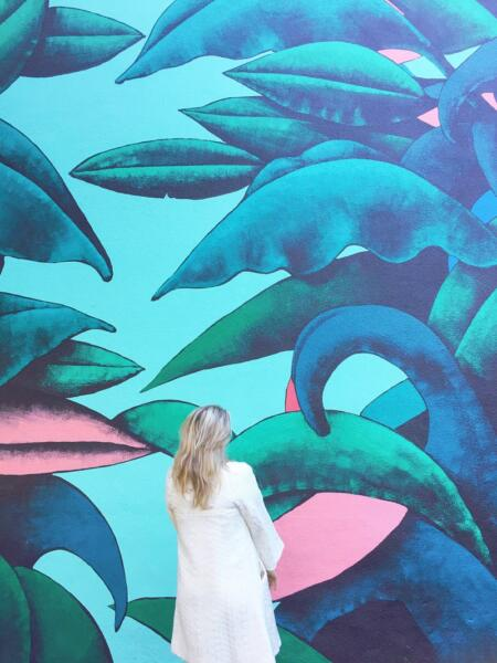 Swayer Carolina in front of blue wall art